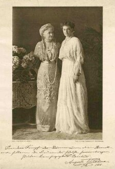 Familienbild, zwei Personen: Kaiserin Auguste Victoria, Königin von Preußen, neben ihr Tochter Prinzessin Viktoria Luise von Preußen in einem Zimmer stehend