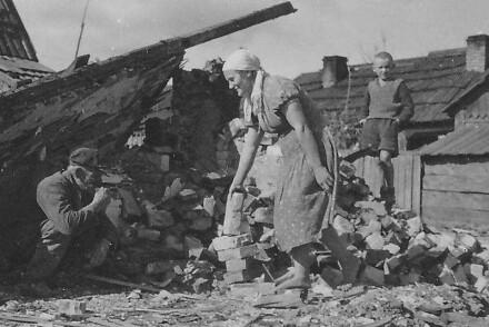 Militärparade. Straßenbau. Gruppen von Frauen. Zerstörtes Dorf.