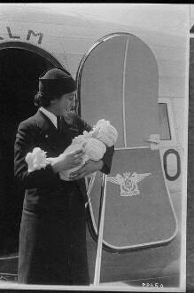 Vergleichsabbildungen. Stewardess mit Säugling vor der geöffneten Tür eines Fugzeuges