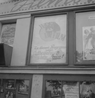 """Alt Buckow (Berlin). Echo Tonfilmtheater Buckow?, Rudower Straße 17. Kinoplakate an der Fassade des Filmtheaters mit Werbung """"Zu diesem Programm zahlen Ostbewohner halbe Preise!"""""""