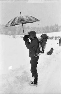 Todtmoos: Internationale Meisterschaften im Hundeschlittenrennen; Mann im Wintersportdress mit Schirm und Kind auf dem Rücken