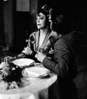 """Kabarett der Komiker: Asta Nielsen; in: """"Kriminalsketch Zimmer 16""""; am Tisch mit Stahl Nachbaur (seitlich gesehen)"""