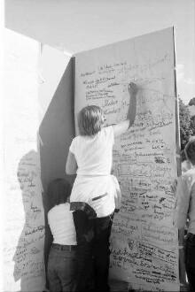 Freiburg: [Kinder schreiben auf Stellwand im Stadtgarten]
